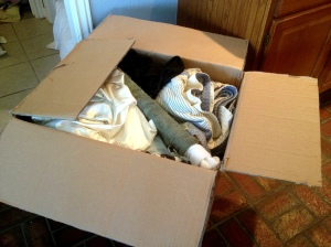 This box contains artwork that has been wrapped in bath towels and surrounded by other similarly wrapped items.